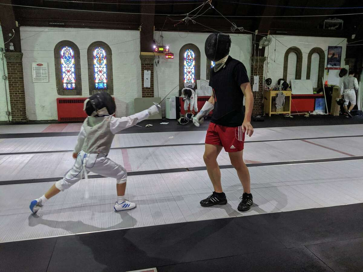 A student practicing fencing with Jim Roberts at the Fairfield Fencing Academy.