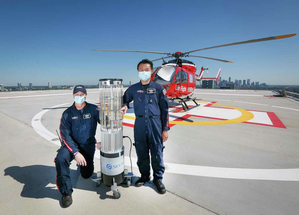 Memorial Hermann Life Flight Nurses Chris Oliver and Rick Liang pose with a state of the art UVC sanitation robot after it disinfected a dedicated helicopter for transportation of COVID-19 patients and Friday, May 1, 2020, in Houston.