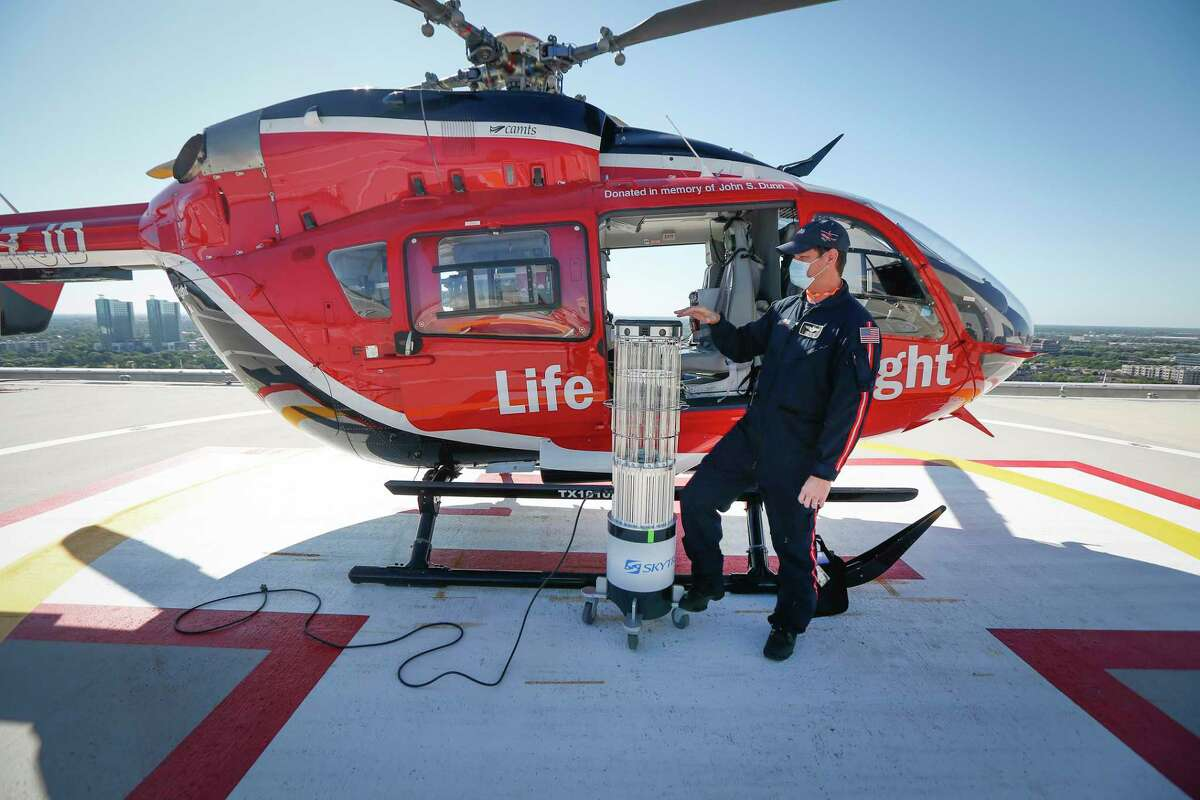 Memorial Hermann Life Flight Nurse Chris Oliver stands next to a dedicated helicopter for transportation of COVID-19 patients and a state of the art UVC sanitation robot Friday, May 1, 2020, in Houston.