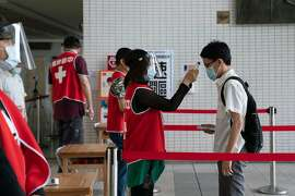 """Pre-class temperature checks at Taipei Municipal Yucheng Senior High School in Taiwan, April 30, 2020. As the coronavirus pandemic lengthens from weeks into months, reminders of the continuing threat have become a part of normal life, even in countries that are beginning to open up: school cafeterias divided by plastic partitions, sports matches played in empty arenas, and """"travel bubbles"""" between countries with few cases. (Ashley Pon/The New York Times)"""