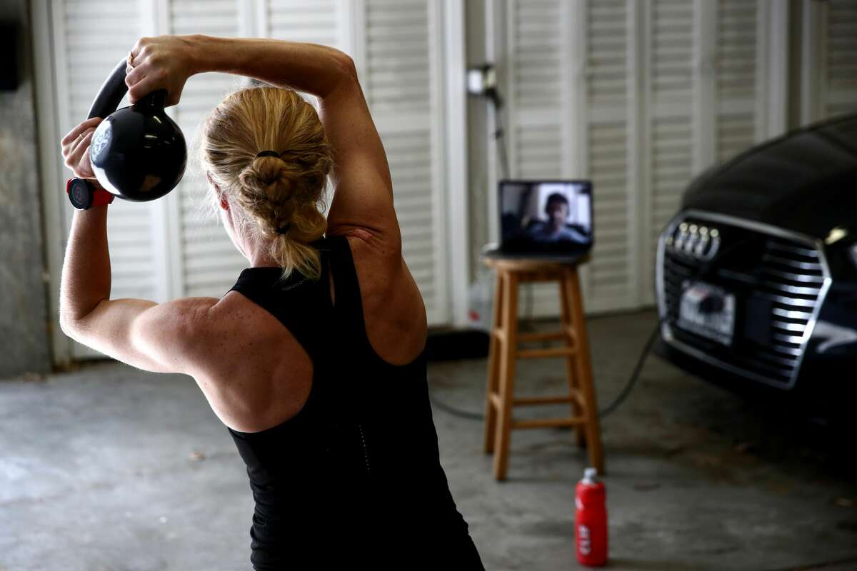 Professional triathlete Sarah Piampiano does a zoom session with her trainer, Charlie Reid, in her carport on April 30, 2020 in Lagunitas, California. Piampiano normally competes in full and half IRONMAN races all over the world, but all her upcoming races have been canceled or postponed due to the coronavirus (COVID-19) pandemic. Piampiano has been mixing up her training with different types of bike riding, road and trail running, swimming in a lagoon instead of a pool, and at home zoom sessions with her trainer.