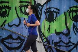 A woman wears a face mask, as a precautionary measure against the COVID-19 coronavirus, as she jogs along a cargo dock dubbed Instagram Pier in Hong Kong on April 21, 2020. - Hong Kong has reduced growth of confirmed COVID-19 cases to single digits in recent days, but city authorities say they are not taking any risks. Chief executive Carrie Lam said social distancing measures and some business restrictions would continue for another two weeks until at least May 7. (Photo by Anthony WALLACE / AFP) (Photo by ANTHONY WALLACE/AFP via Getty Images)