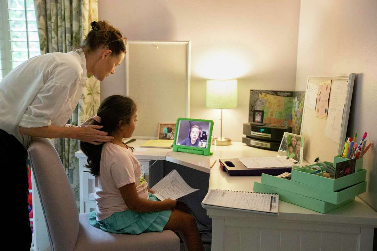 Quenby Mott helps her daughter, Sydney Mott, 9, sets up a 30-minute Zoom meeting with Kinkaid School 10th-grader Clayton Rice Tuesday, May 5, 2020, in Houston.