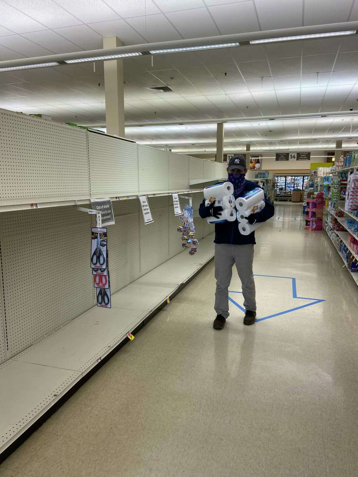 A masked customer is stocking up on needed paper supplies amid the nearly empty supermarket shelves.