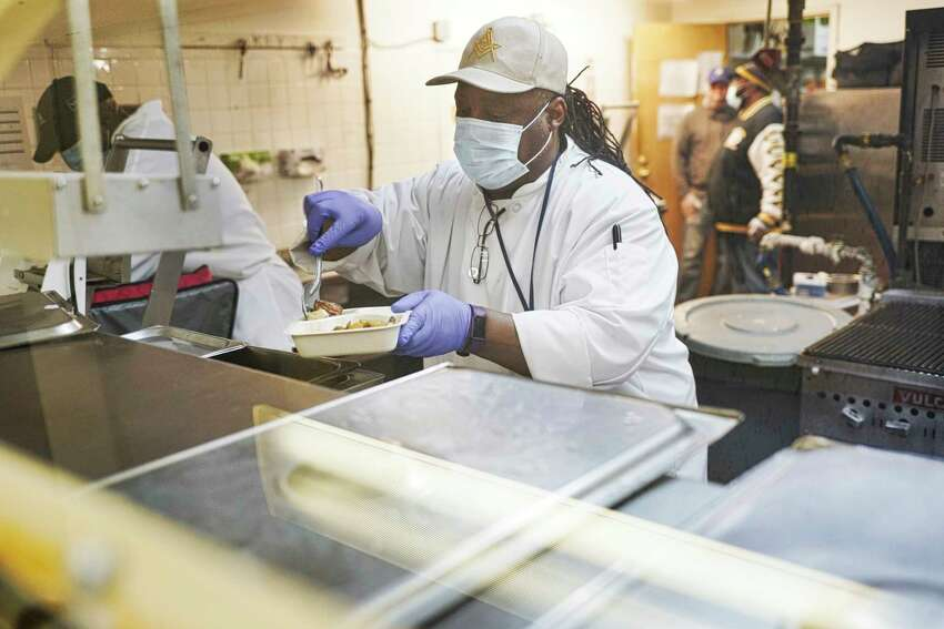 Darryl Clark, the chef manager at the Peter Young Housing, Industries, and Treatment organization, fills meal trays with food on Thursday, May 7, 2020, in Menands, N.Y. Along with the 250 meals a day for the senior home meal food delivery program, workers are also prepping meals that will be distributed on Friday at 45 South Ferry from 10am to 2pm or earlier if all the food is given out. The meals are open to anyone in need. (Paul Buckowski/Times Union)