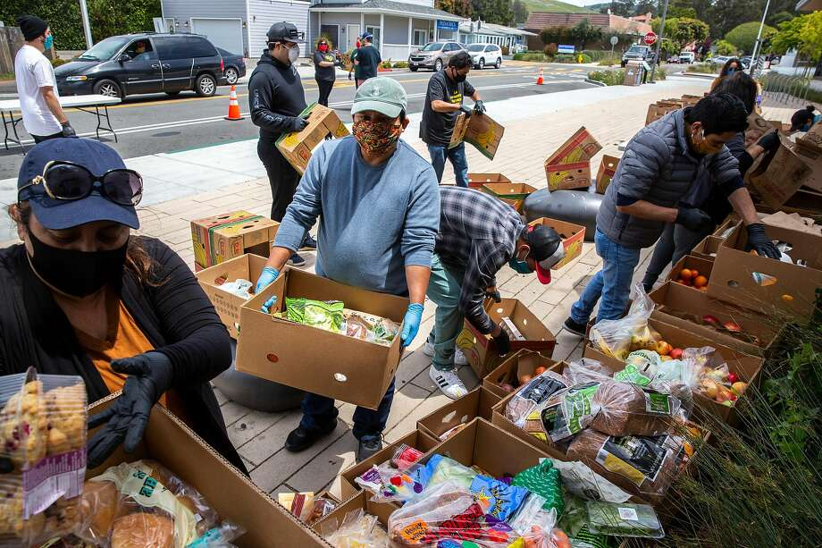 Volunteers Juana Ruano (left) and Julio Lopez organize food donations at a drive-through site in Half Moon Bay. Those in need get a box of food and gift cards without leaving their vehicles. Photo: Santiago Mejia / The Chronicle