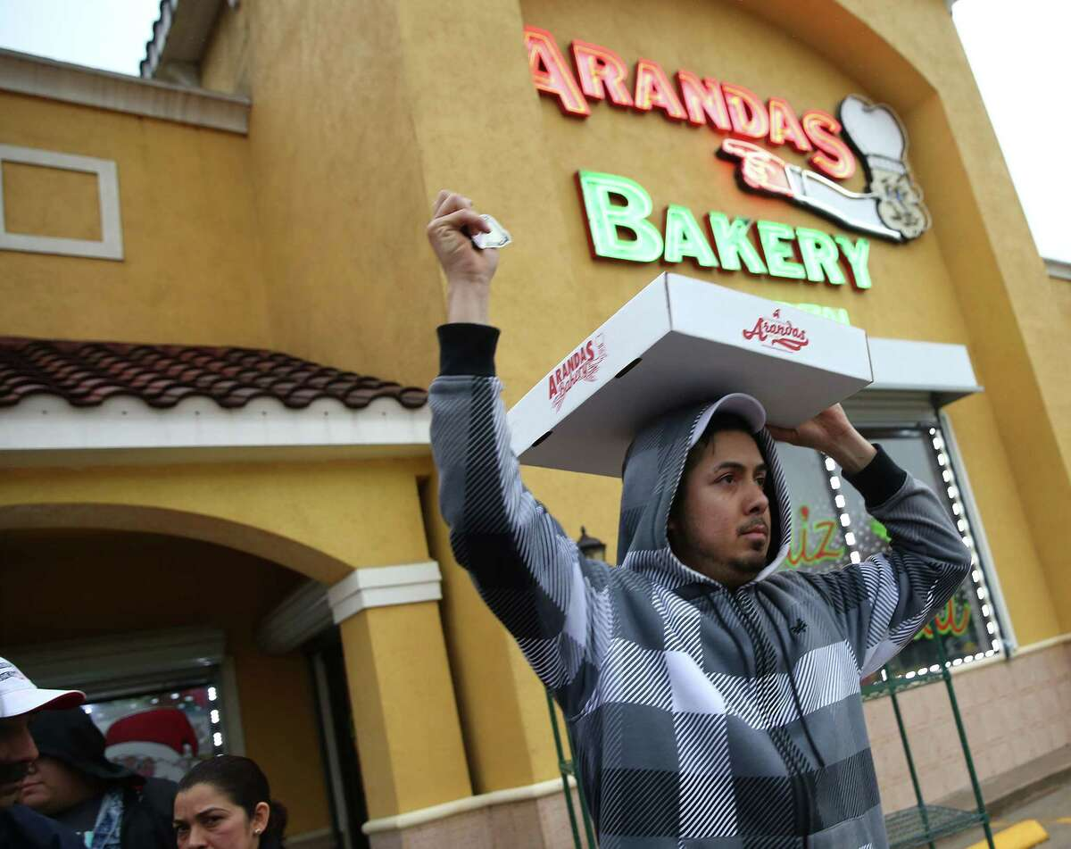 Armando Lazcano holds a King Cake on his head as he delivers to cars lined up outside Arandas Bakery during its commemoration of the Epiphany on Wednesday, Jan. 6, 2016, in Houston.