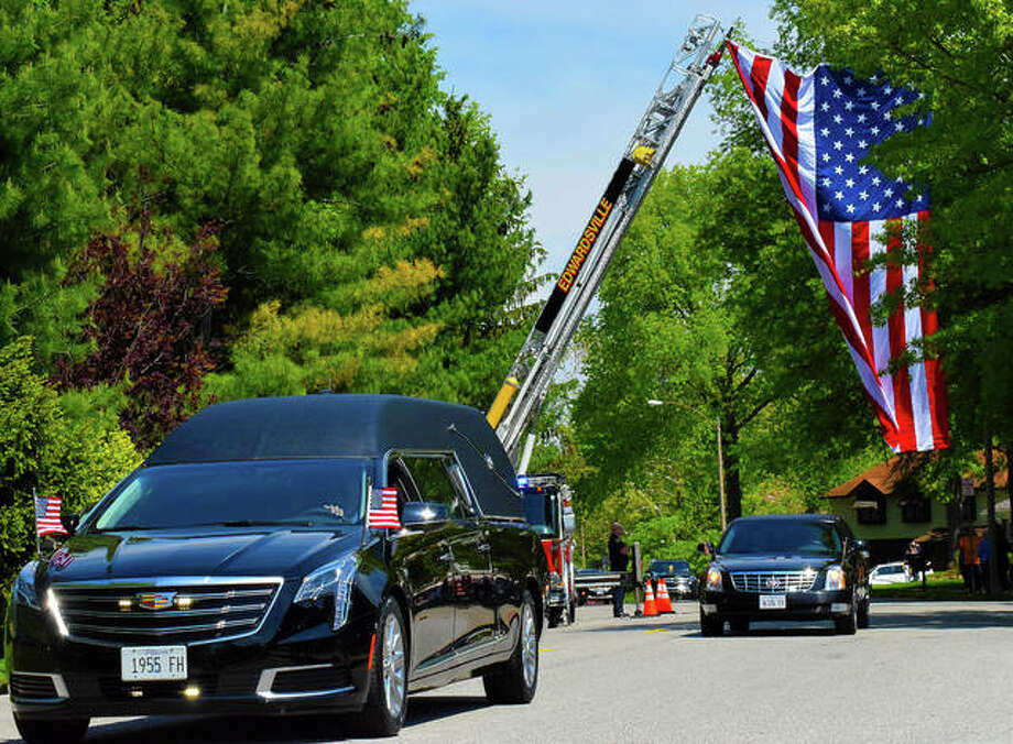 A hearse carrying former mayor of Edwardsville, Gary Niebur, passed under a flag lifted by the Edwardsville Fire Department in front of the YMCA's Niebur Center on Esic Drive at 11:15 a.m. Thursday in Edwardsville. Niebur died on Saturday at the age of 64. Photo: Tyler Pletsch | The Intelligencer