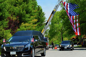 A hearse carrying former mayor of Edwardsville, Gary Niebur, passed under a flag lifted by the Edwardsville Fire Department in front of the YMCA's Niebur Center on Esic Drive at 11:15 a.m. Thursday in Edwardsville. Niebur died on Saturday at the age of 64.