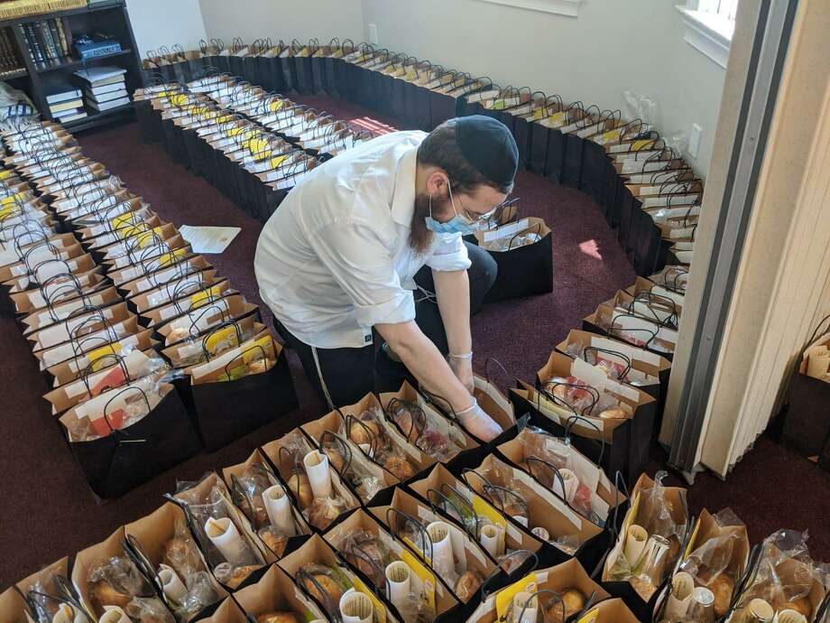 Volunteer Levi Deren packs a Shabbat gift bag that is being offered by Chabad Lubavitch of Greenwich to its community. The Shabbat gift bags are being delivered to 500 people/families in the Jewish community, in an effort to raise spirits during the challenging times the COVID-19 crisis has presented. Photo: Contributed Photo