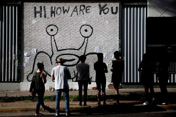 """People pay their respects at the """"Hi, How Are You"""" mural created by artist Daniel Johnston on Wednesday, Sept. 11, 2019, in Austin, Texas. Johnston, a quirky folk singer-songwriter and visual artist whose offbeat career and struggles with mental illness brought him a cult following and inspired a documentary film, has died at age 58. According to a statement issued by his family, Johnston died of natural causes Wednesday morning at his Houston-area home. (Nick Wagner/Austin American-Statesman via AP)"""