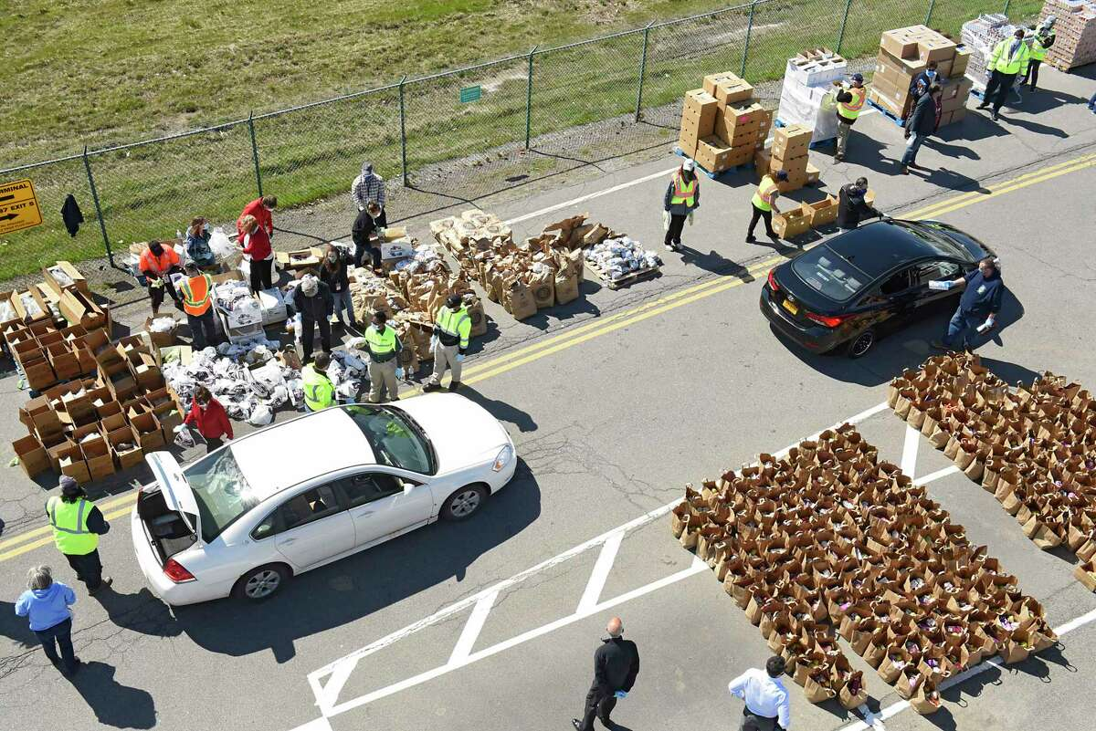 Volunteers load food in hundreds of cars which lined up halfway around the airport during a Northeast Regional Food Bank distribution at the Albany International Airport on Thursday, May 7, 2020 in Albany, N.Y. Albany International Airport and Regional Food Bank partnered for this drive-thru food pantry to help people in need during the COVID-19 crisis. (Lori Van Buren/Times Union)