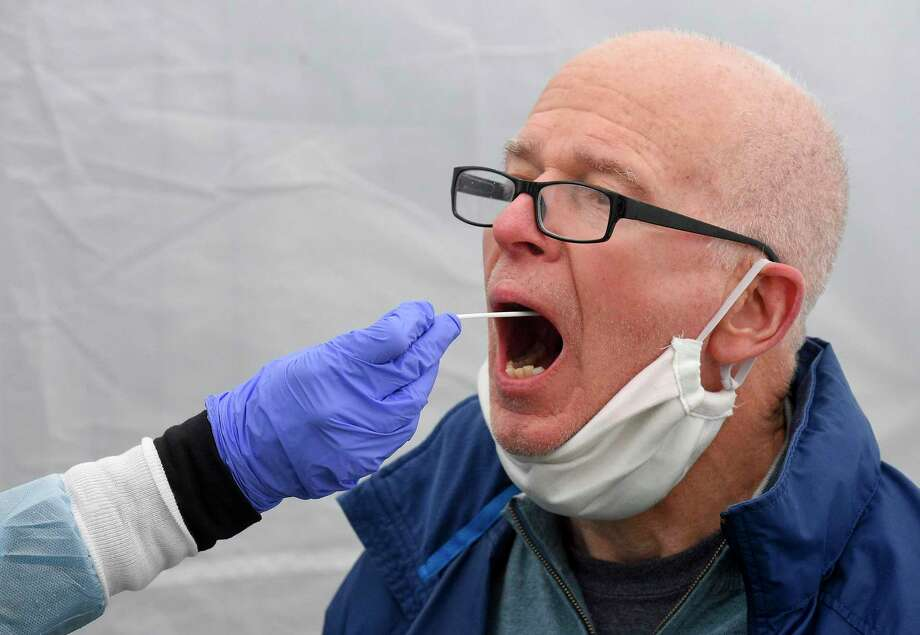 Greenwich resident Larry Heath, 73, is given an Rapid Oral COVID-19 test at a testing site set up at the Family Center at Wilbur Peck Court in Greenwich in May. An increase in town cases was reported over the past week, but the town is not in a red alert area like some other places in Connecticut. Photo: File / Matthew Brown / Hearst Connecticut Media / Stamford Advocate