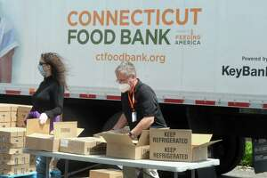 Thousands of people arrived by car to take part in Connecticut Food Bank's drive-thru food donation in Bridgeport, Conn. May 7, 2020. The event distributed an estimated 32-tons of food, enough to provide approximately 50,000 meals.