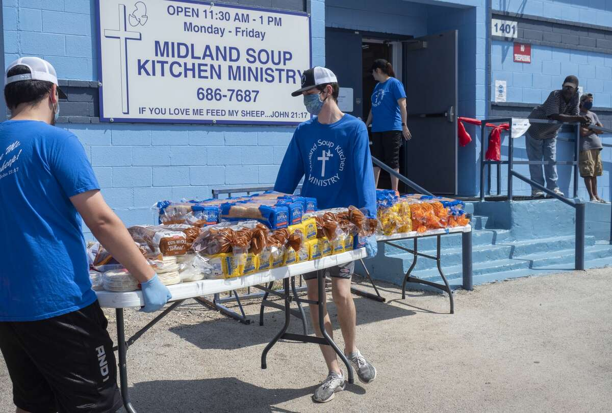 Jay Anthony Ivy, left, and his brother Nathen Ivy place the tables outside the Midland Soup Kitchen 05/07/2020 for customers to take a loaf of bread with them after picking up to-go meals from the front door. The dining area is still closed, but hot meals are being served to-go. Tim Fischer/Reporter-Telegram