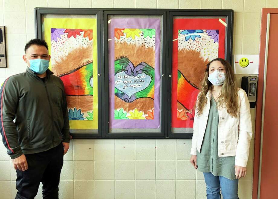 From left, state Department of Children and Families Albert J. Solnit Center employees, assistant rehabilitation therapist John Fontanez and rehabilitation art therapist Heather Cassella, show off artistic panels created by girls staying at the psychiatric facility. Creating art often helps these teens work through their issues as well as demonstrate their compassion for first responders and staff dealing with the coronavirus outbreak. Photo: Contributed Photo