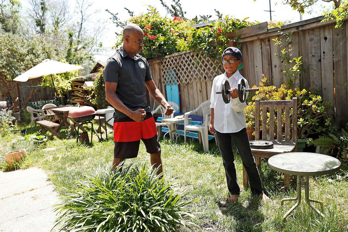Jason Gittens encourages his son, Kekoa, 9, as he does curls as the PE portion of his virtual school day at their residence in San Rafael, Calif., on Wednesday, May 6, 2020. Gittens ia gaffer and cameraman that has had his work totally dry up during pandemic and ensuing shelter in place.