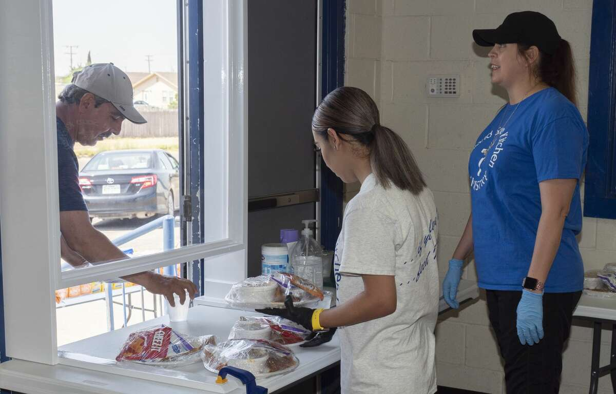 Karen Munoz and Nancy Ivy ready meals to-go at the Midland Soup Kitchen 05/07/2020 for customers to pick from the front door. The dining area is still closed, but hot meals are being served to-go. Tim Fischer/Reporter-Telegram