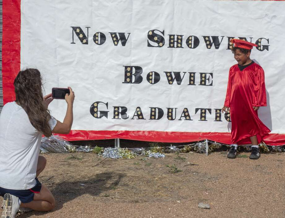 Hope Harrold takes pictures of her son Cade 05/07/2020 outside Bowie Fine Arts Academy. Bowie kindergarten teachers let parents know there would be a banner outside the school, and cap and gowns available for pictures, and then ask parents to email the pictures in for a video to be made of all the graduates. Tim Fischer/Reporter-Telegram Photo: Tim Fischer/Midland Reporter-Telegram