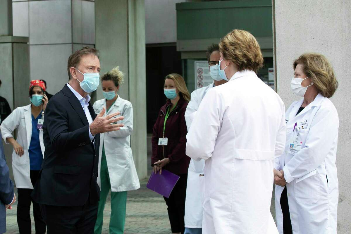 Connecticut Gov. Ned Lamont, left, talks with medical staff outside Saint Francis Hospital, Thursday, May 7, 2020, in Hartford, Conn. He made a visit to the medical center to thank the healthcare workers for their efforts during the coronavirus pandemic. (AP Photo/Mark Lennihan)