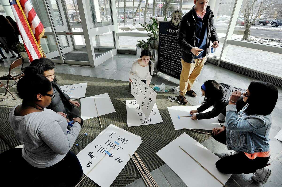 Members of the Stamford Youth Services Bureau Center for Youth Leadership put the finishing touches on signs before the start of the National Teen Dating Violence Awareness Month press conference at the Stamford Government Center in Stamford, Conn., on Thursday, Jan. 29, 2015.
