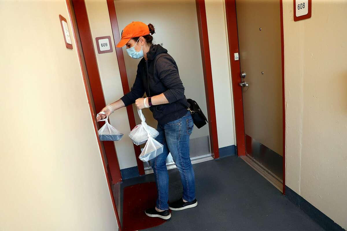 Debbie Tisdale delivers meals to seniors at Ping Yuen Central housing project as part of Chinatown Community Development Center food distribution program in San Francisco, Calif., on Monday, May 4, 2020.