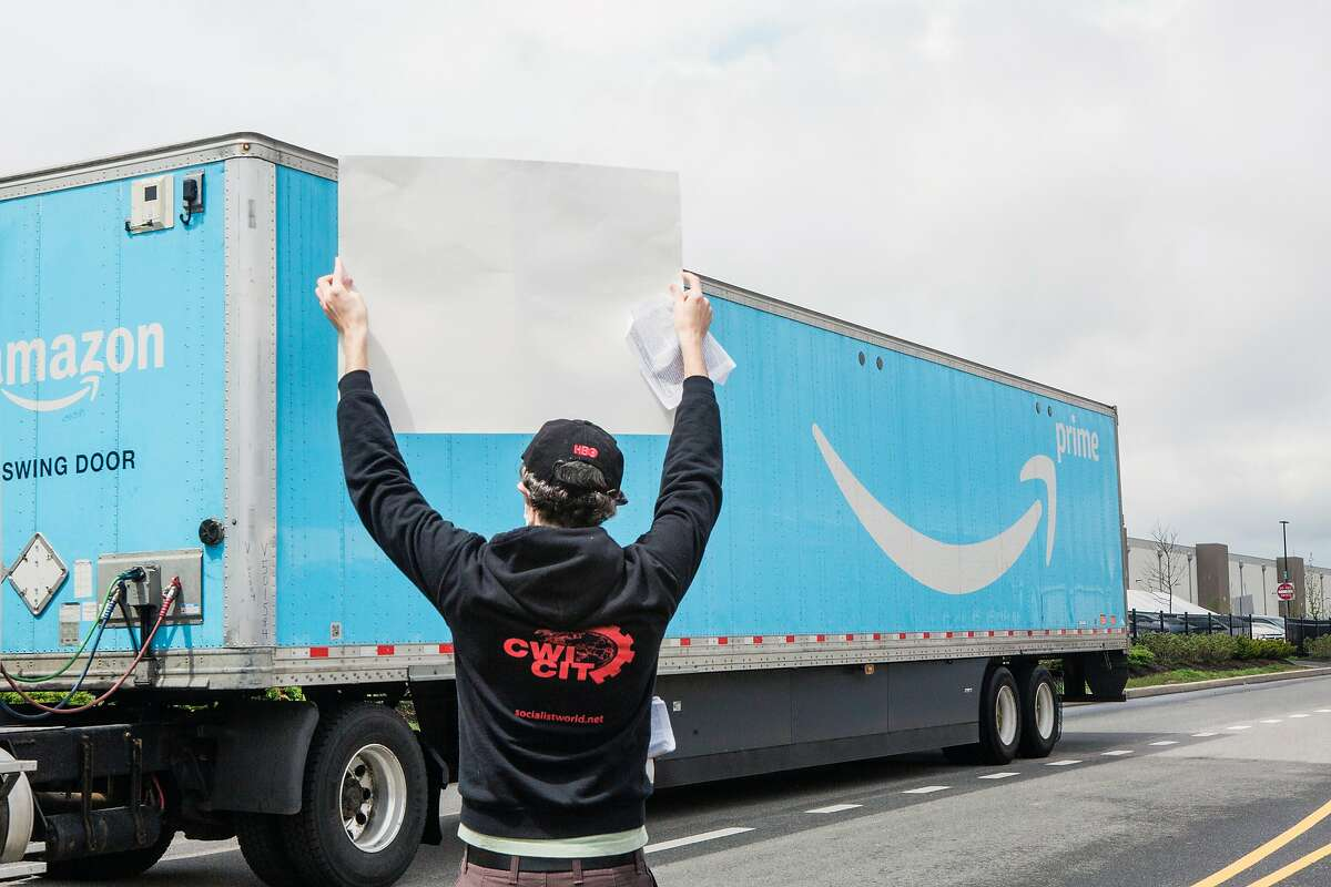 FILE -- A protester holds up a sign during a demonstration outside an Amazon warehouse in Staten Island on May 1, 2020, calling for more workplace protections during the coronavus pandemic. Democratic senators on Thursday, May 7, 2020, questioned whether Amazon retaliated against whistle-blowers when it fired four employees who raised concerns about the spread of coronavirus in the company's warehouses.