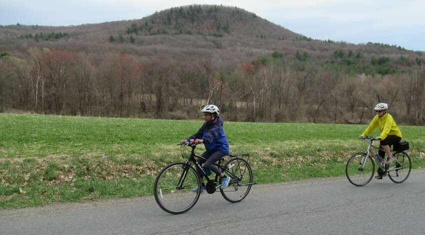 Gillian Scott, right, and her daughter ride Burton Road with Willard Mountain behind them. (Herb Terns / Times Union)