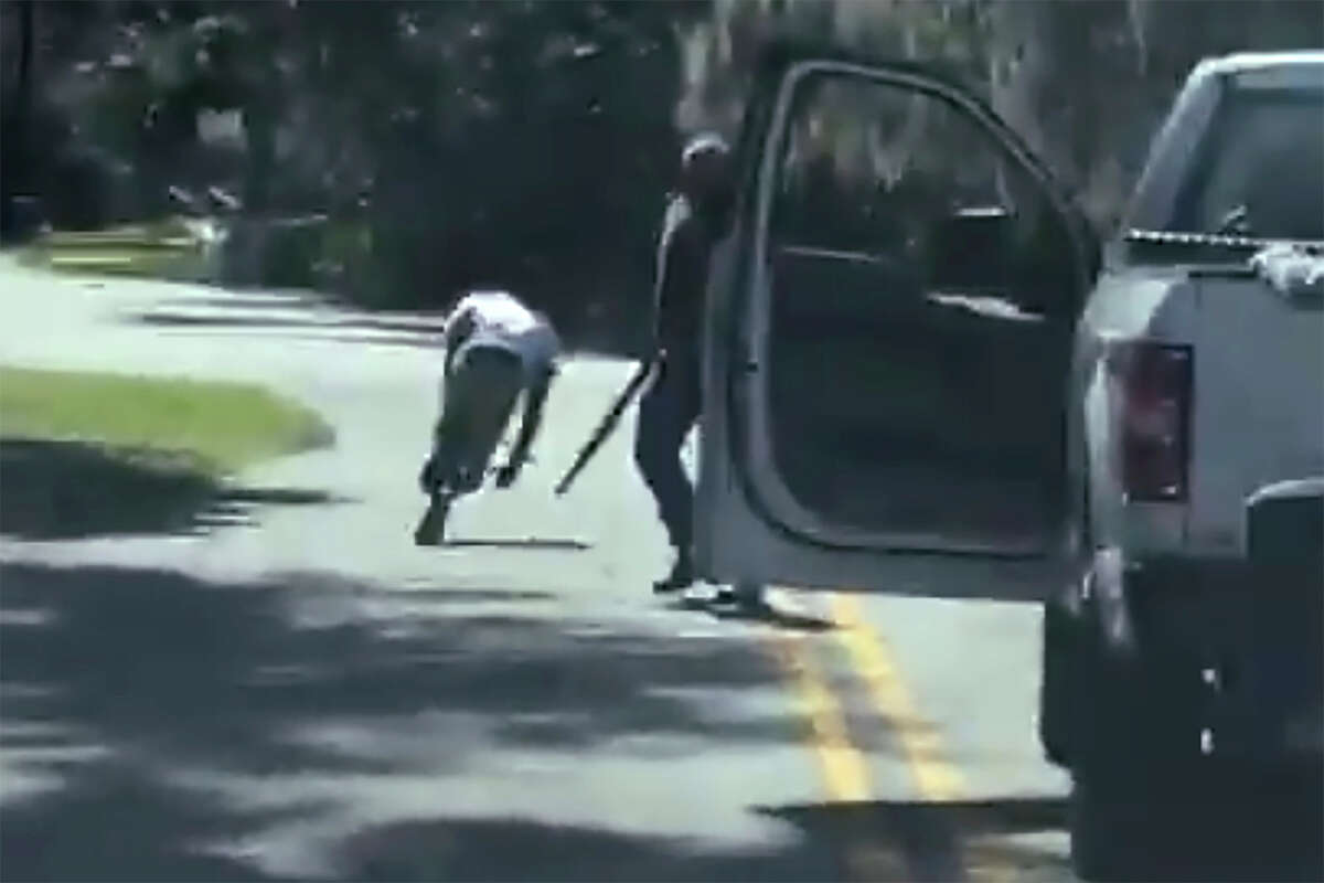 This image from video posted on Twitter Tuesday, May 5, 2020, purports to show Ahmaud Arbery stumbling and falling to the ground after being shot as Travis McMichael stands by holding a shotgun in a neighborhood outside Brunswick, Ga., on Feb. 23, 2020. The AP has not been able to verify the source of the video. (Twitter via AP)