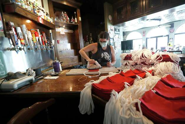 Bartender Sarah Miller irons masks on the bar inside of the Maple Leaf Pub, in Houston, Thursday, May 7, 2020. Courtney and Micahl Wyckoff started making masks out of their home after both finding themselves out of work because of coronavirus. Courtney, a seamstress, used leftover fabric she had lying around the house to start making the mask. They also started hiring their other out of work friends to help them. Their business is Grab Bag Masks.com. Photo: Karen Warren, Staff Photographer / © 2020 Houston Chronicle