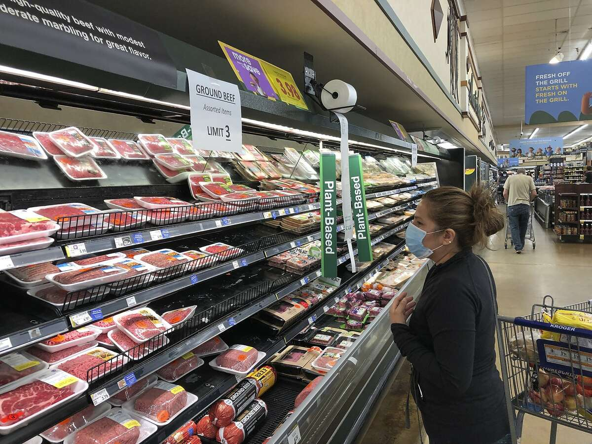 A shopper looks beef at a Kroger store in Atlanta underneath a sign limiting shoppers to three packages of ground beef on Tuesday, May 5, 2020. Kroger is limiting meat purchases, like a number of other grocery retailers, due to supply concerns amid the COVID-19 pandemic. (AP Photo/Jeff Amy)