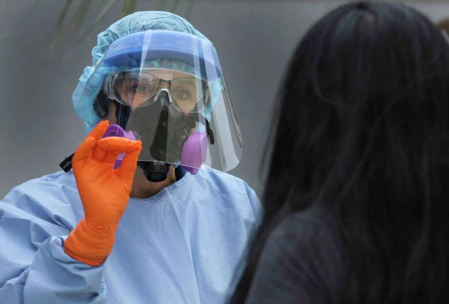 A San Antonio fire fighter dressed in protection gear explains the COVID-19 testing procedure to a woman at Las Palmas Public Library, on Thursday, May 7, 2020. Photo: Bob Owen /San Antonio Express-News / ©2020 San Antonio Express-News