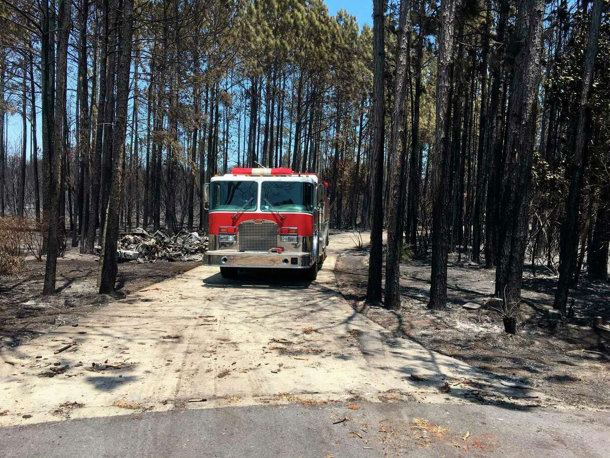 A fire engine sits in a burned residential neighborhood in Walton County, Fla., Thursday morning, May 7, 2020, following an overnight wildfire that destroyed more than two dozen home. (Tom McLaughlin/Northwest Florida Daily News via AP)