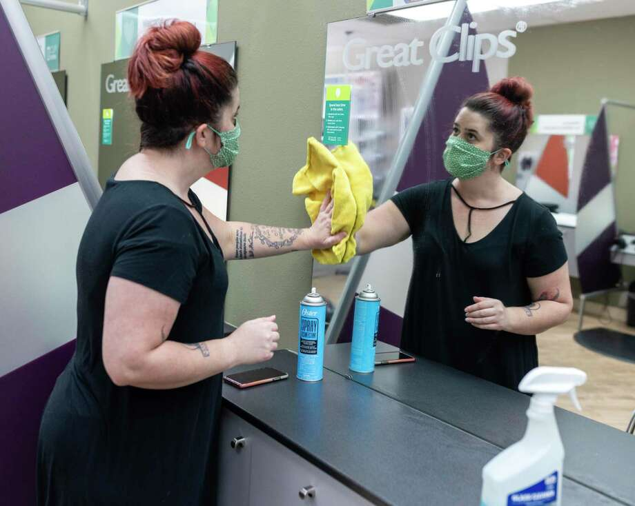 Elisabeth Willason, assistant manager at Great Clips in Conroe, wipes down a mirror, Thursday, May 7, 2020. Gov. Greg Abbott ordered all nonessential businesses such as salons and nail tech services to be shut down since mid-March but will allow businesses to open this Friday. Photo: Gustavo Huerta, Houston Chronicle / Staff Photographer / Houston Chronicle © 2020