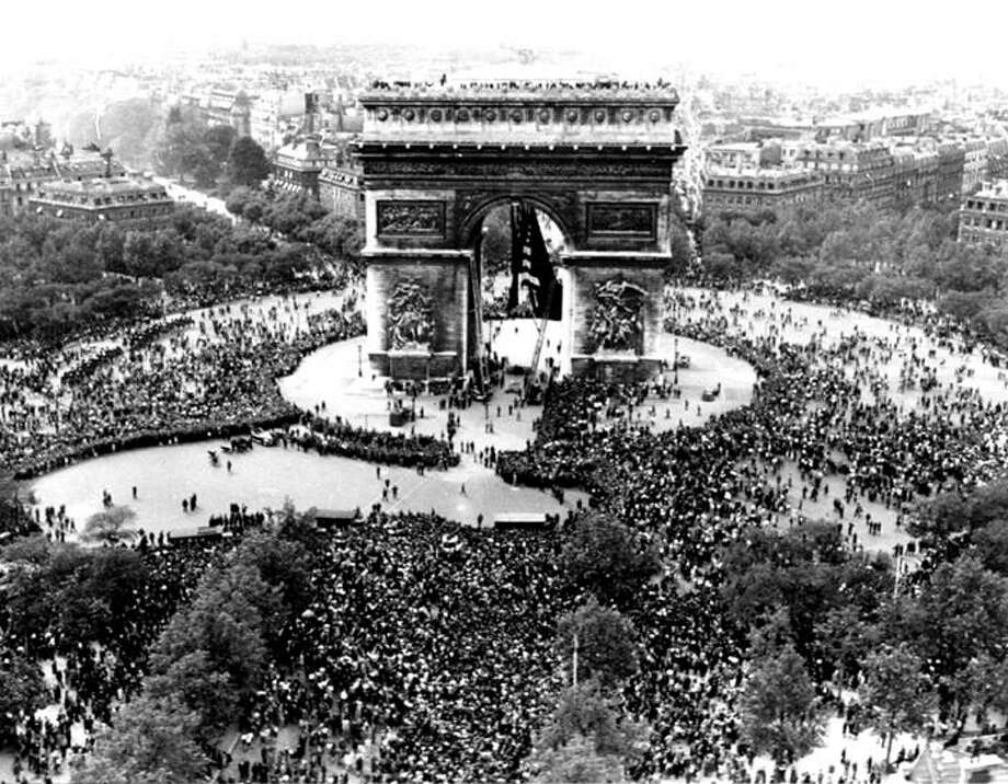 This is an aerial view of the Arc de Triomphe in Paris on VE Day, May 7, 1945, shows thousands of French people celebrating the announcement of Germany's unconditional surrender to the Allies. British, American and French servicemen mingled with the crowds who sang and danced throughout the night. Photo: (AP Photo)
