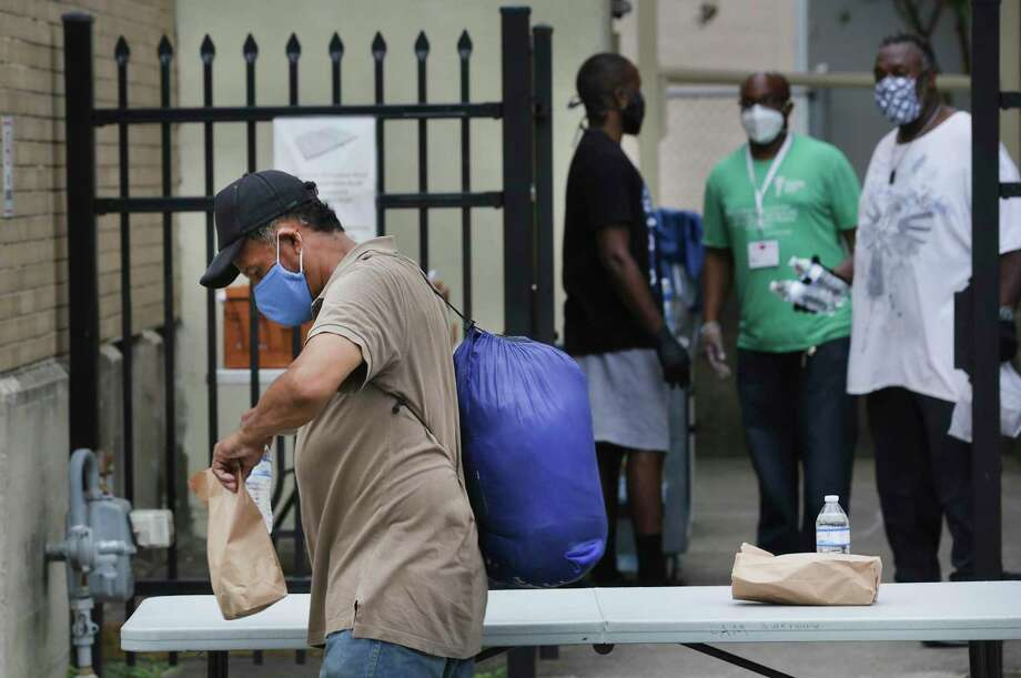 A homeless man looks at the sack meal he received from workers, right, at Christian Assistance Ministry, which received a $50,000 grant recently. During the coronavirus pandemic, people who are homeless have fewer locations to receive food. Photo: Bob Owen /Staff Photographer / ©2020 San Antonio Express-News