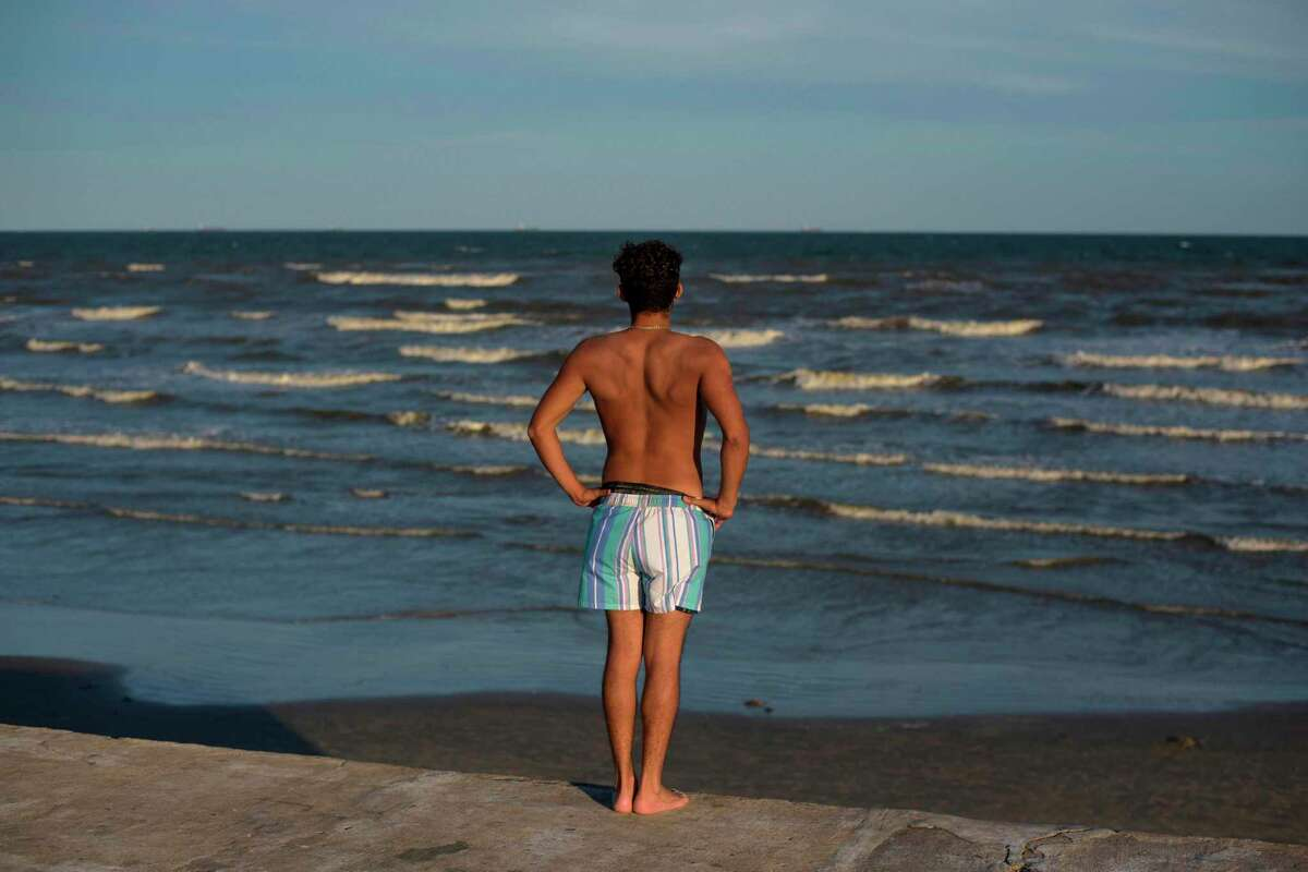 A beachgoer looks out over Galveston Beach on May 2, 2020 in Galveston, Texas, amid the coronavirus pandemic. - Texas beaches were ordered to be opened on May 1, 2020. In a statement, the City of Galveston said,
