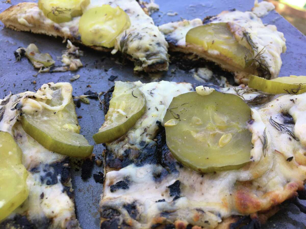 A finished dill pickle pizza comes off hot off the grill at Chuck's Food Shack.