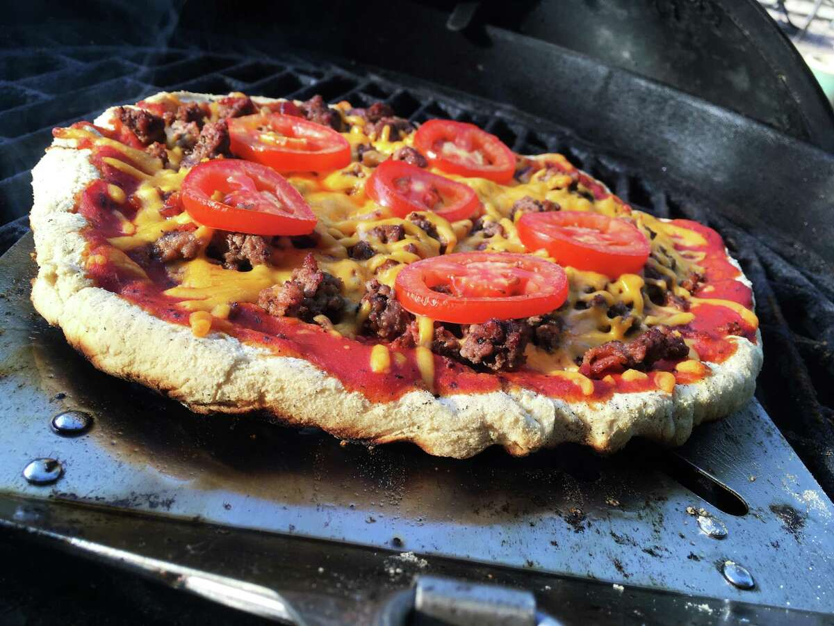 A bacon cheeseburger pizza is tossed on the grill for a quick cooking process.