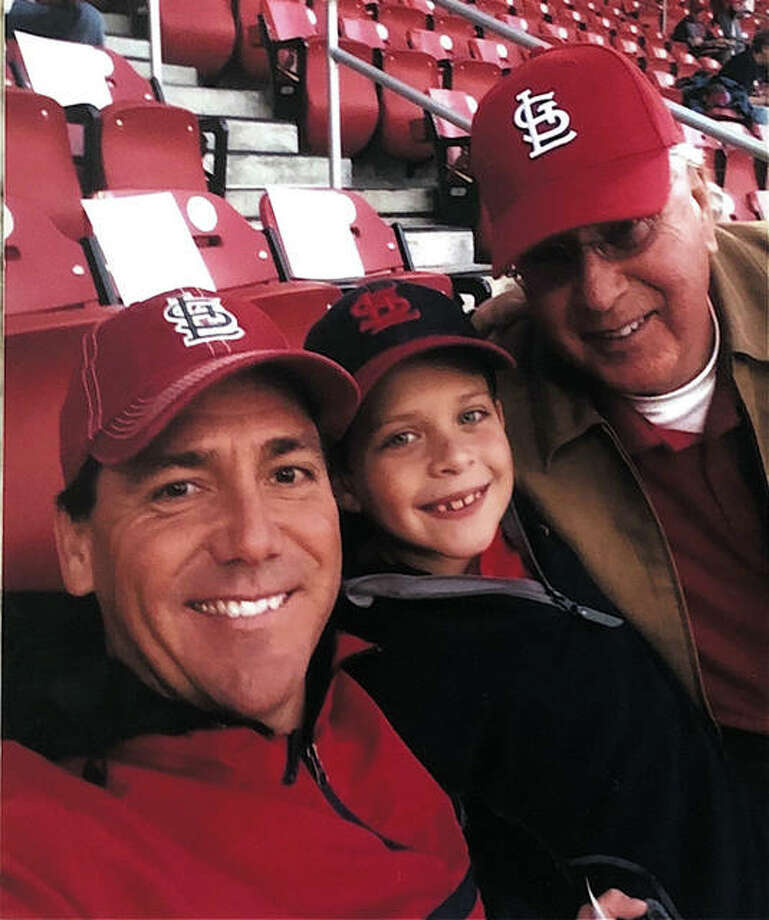 Former Edwardsville state champion swimmer Bill Stapleton, left, his son, Ben, and his father, William, attend a St. Louis Cardinals World Series game in 2013. Photo: Submitted Photo
