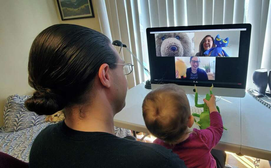 Thomas and Aurelia Kozak, 14 months, watching Stuffed Animal Picnic Storytime. The Youth Services librarians on screen are Anna Taylor (teddy bear), Kaitlin Frick (blue cat), and Samantha Cardone (yellow pony). Photo: Contributed Photo / / Connecticut Post