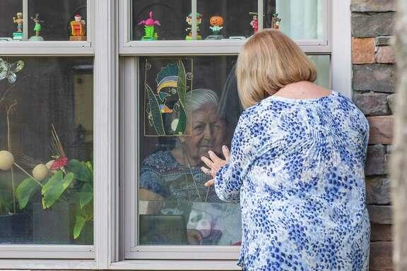 Laurel Parker visits mom Winnie Byrnes outside her room in Sunrise assisted living facility.