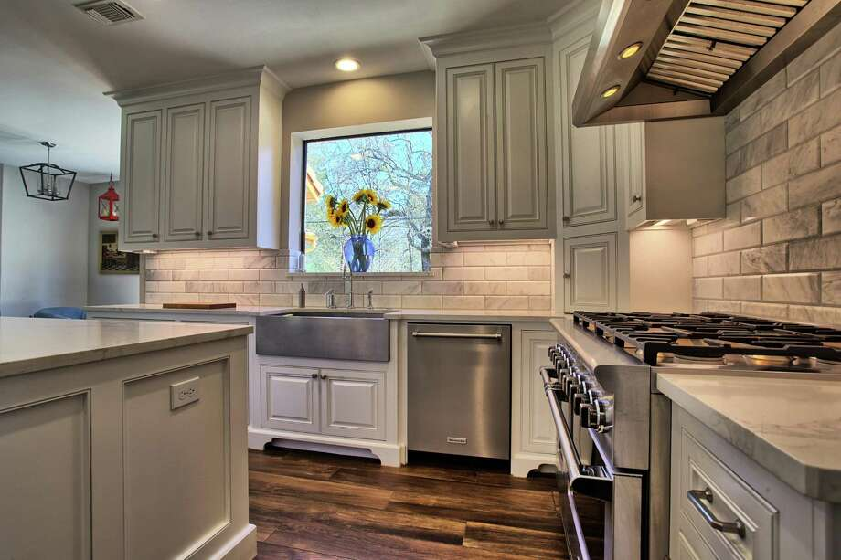 This kitchen remodel features quartzite counters and a stainless-steel farmhouse sink.