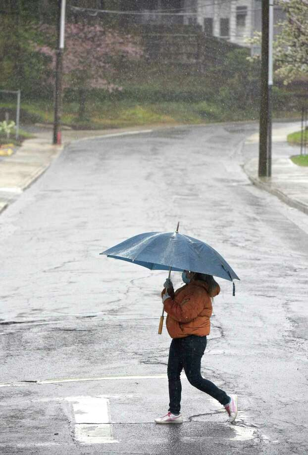 A pedestrian crosses Chapel Place while walking down Main Street during the rain April 13 in Danbury. Photo: H John Voorhees III / Hearst Connecticut Media / The News-Times