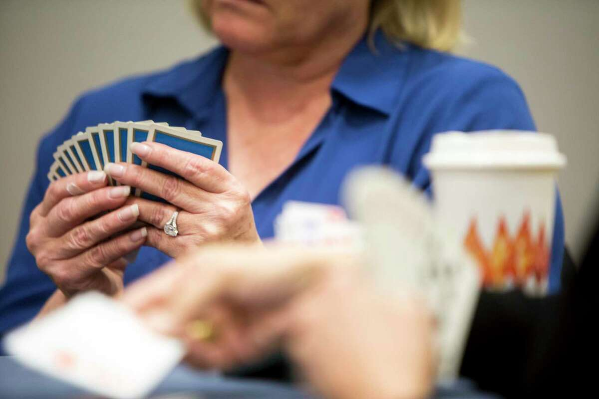 Lolly Prince holds her cards closely while Penny Foote plays a card during a bridge game. Steve Becker teaches a weekly two hour class at the Greenwich YWCA to a class of about 40 people on Friday, October 27, 2017. The class begins with tables of four playing hands preselected to isolate play from luck. After the class practices he charts out their gameplay giving him the chance to critique their choices.