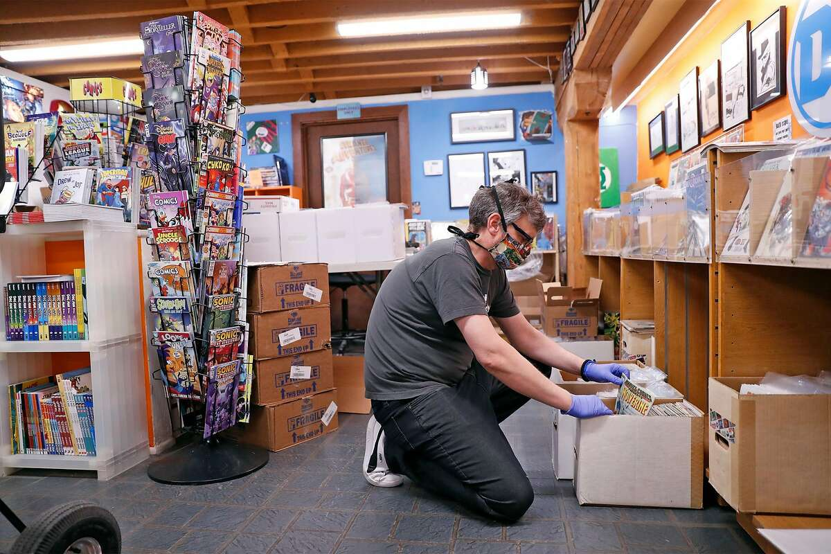 Brian Christensen, owner of Brian's Comics, fulfills a customer's order at his store in Petaluma, Calif., on Thursday, May 7, 2020. Christensen has been operating as an online only operation, but starting May 8th, Sonoma County non-essential businesses like florists, bookstores and clothing stores, will be able to offer curbside pick up.