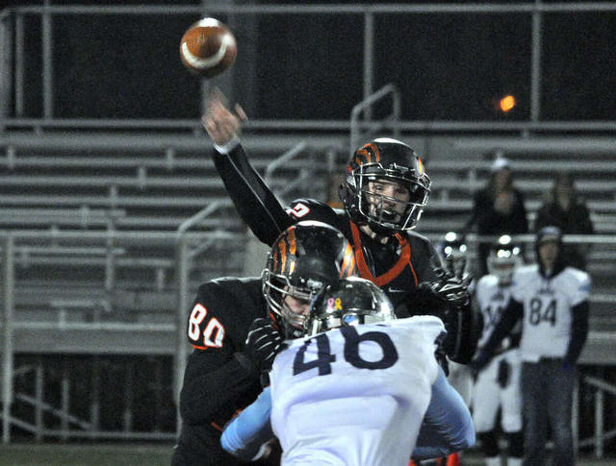 Edwardsville quarterback Dan Marinko, back, fires a pass to a receiver while his lineman Nathan Crone (No. 80) blocks Belleville East linebacker Dustin Stone.