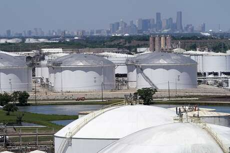 In this Thursday, April 30, 2020, photo storage tanks along the Houston Ship Channel are seen with downtown Houston in the background. Like in other cities, the coronavirus has shut down much of Houston's economic activity, slashing thousands of jobs, while at the same time, the price of oil plunged below zero recently as demand plummeted due to the worldwide lockdown to stop the spread of the virus. This one-two punch from COVID-19 and the collapse in oil prices will make it much harder for Houston to recover from a looming recession, according to economists. (AP Photo/David J. Phillip)