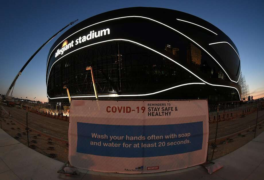 A sign with guidelines for coronavirus safety is posted on a fence as construction continues at Allegiant Stadium in Las Vegas. Photo: Ethan Miller / Getty Images