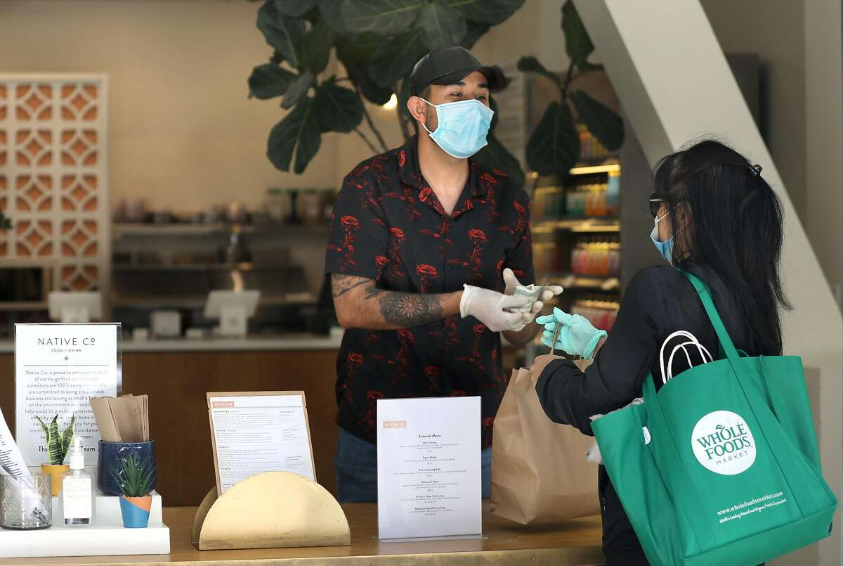 Cashier Erick Rios (left) gives an order to Cecile Catig (right) at Native Co. on Thursday, May 7, 2020, in San Francisco, Calif.